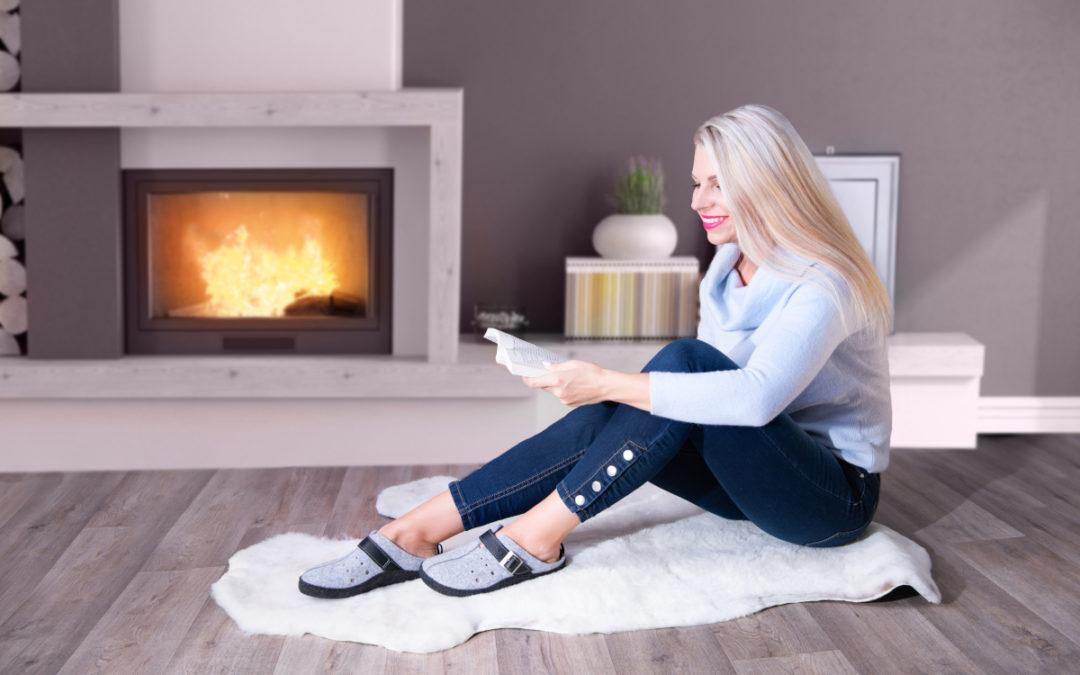 Kobieta czytająca książkę przy kominku. Na stopach ma szare klapki ortopedyczne.